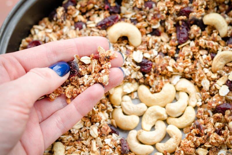 De vrouwelijke hand houdt granola tegen de achtergrond van bakselblad royalty-vrije stock foto's