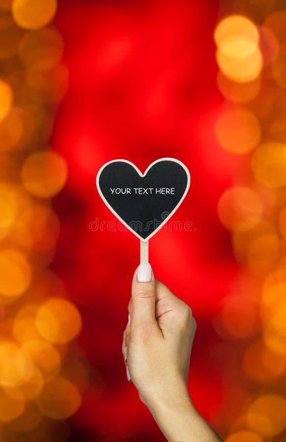 De vrouwelijke hand houdt hartteken stock foto