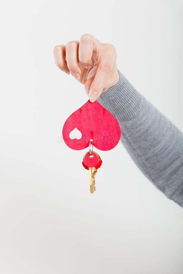 De vrouwelijke hand houdt weinig hart met sleutels royalty-vrije stock foto