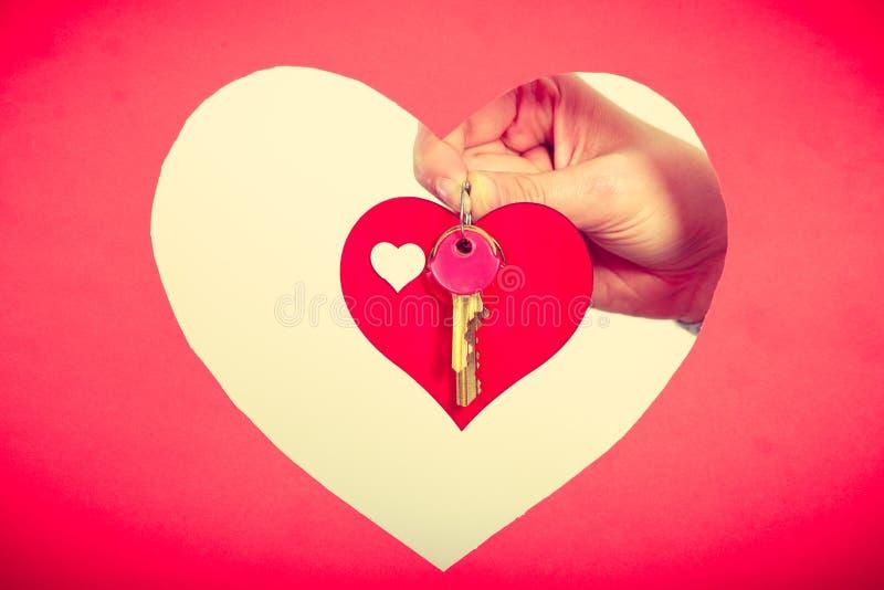 De vrouwelijke hand houdt weinig hart met sleutels stock foto's