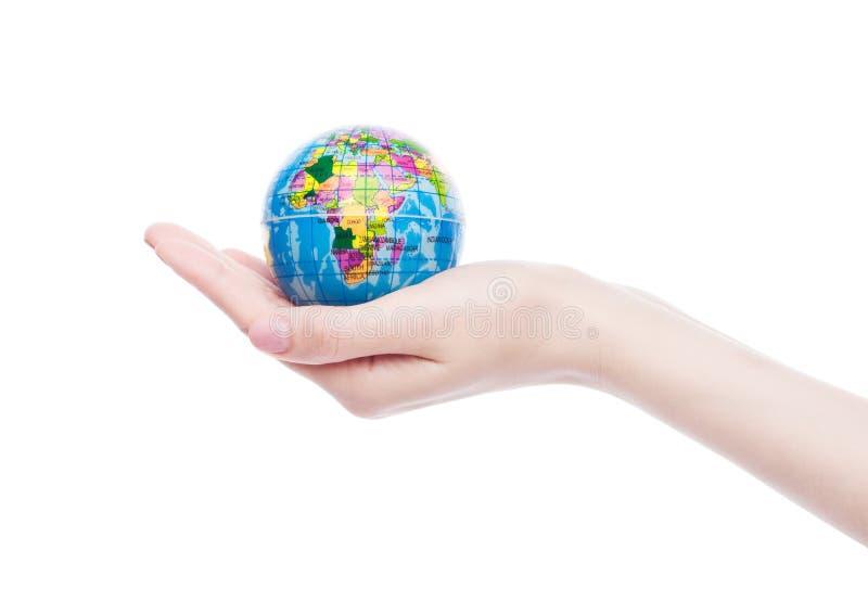 De vrouwelijke hand houdt wereldbol op witte achtergrond stock foto's