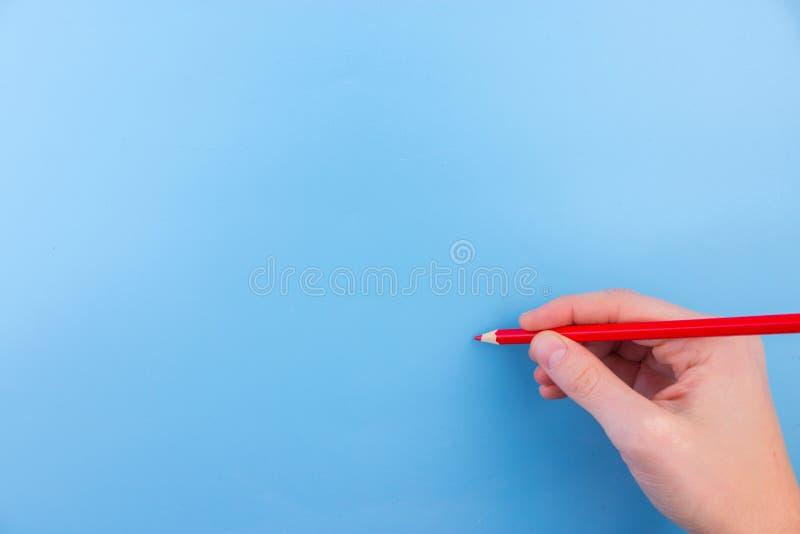 De vrouwelijke hand is klaar voor tekening met rode teller stock fotografie
