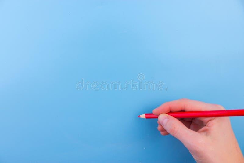 De vrouwelijke hand is klaar voor tekening met rode teller stock afbeelding