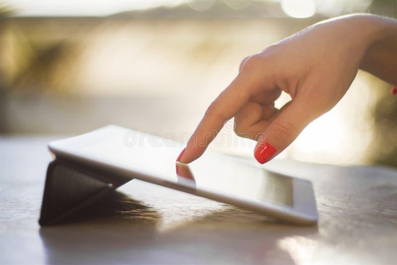 De vrouwelijke hand klikt op een digitale tablet stock foto