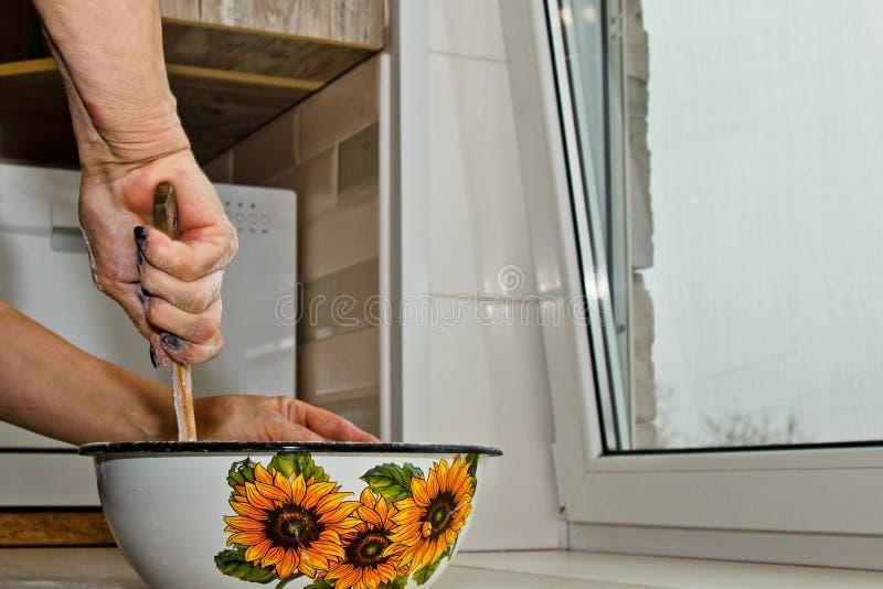 De vrouwelijke hand kneedt deeg van melk van boter en de bloem in een metaalkom met houten zwaait in de keuken stock foto