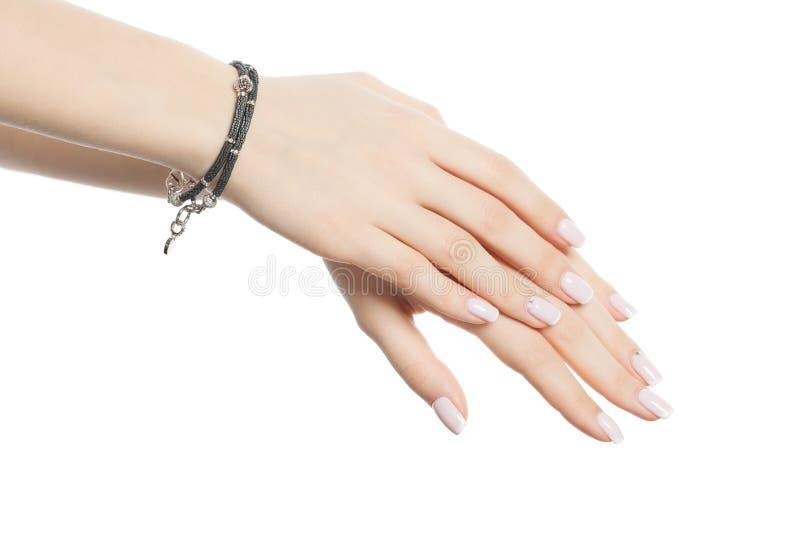 De vrouwelijke hand met armband en manicured spijkers met Franse die manicure op witte achtergrond wordt geïsoleerd stock afbeelding