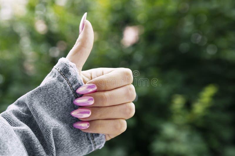 De vrouwelijke hand met een mooie roze manicure toont klasse stock afbeelding