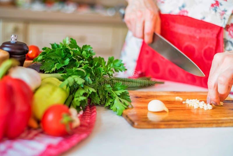 De vrouwelijke hand met mes hakt knoflook in keuken Kokende groenten royalty-vrije stock fotografie