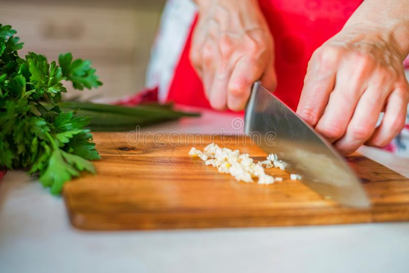 De vrouwelijke hand met mes hakt knoflook in keuken Kokende groenten royalty-vrije stock afbeelding