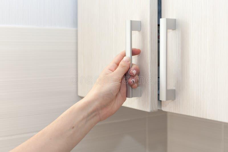 De vrouwelijke hand opent de kastdeuren, omhoog sluit stock afbeeldingen