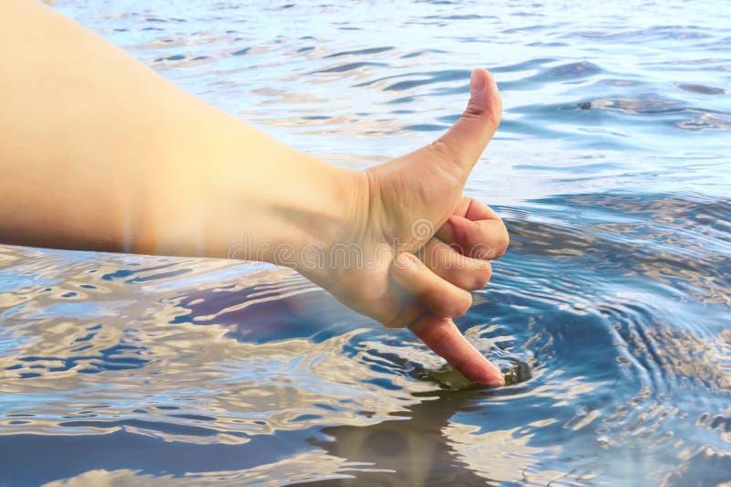 De vrouwelijke hand raakt het water met een vinger en toont aan dat het warm en schoon is De zomervakantie en het zwemmen concept royalty-vrije stock afbeeldingen