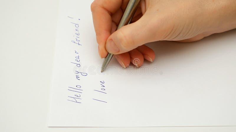 De vrouwelijke hand schrijft I-liefde u op het document blad stock afbeelding