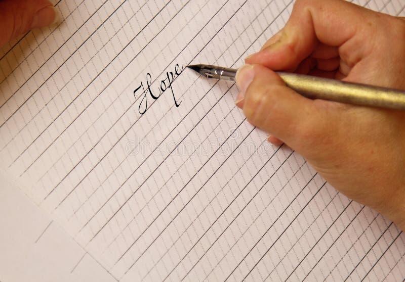 De vrouwelijke hand schrijft met de met inkt besmeurde pen de woordhoop op een Witboekblad met strepen kantoorbehoeften op bureau royalty-vrije stock foto's