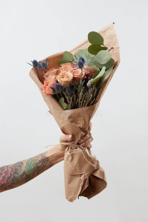 De vrouwelijke hand toont boeket met roze bloemen op grijze achtergrond Gift voor Moeder of van de Vrouw Dag stock foto