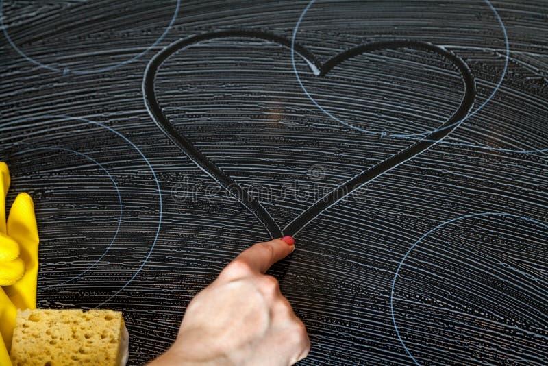De vrouwelijke hand trekt hart op witachtige oppervlakte stock afbeelding