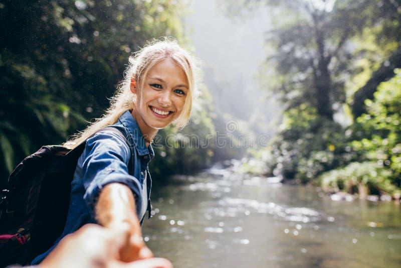 De vrouwelijke hand van de wandelaarholding van zijn vriend royalty-vrije stock fotografie