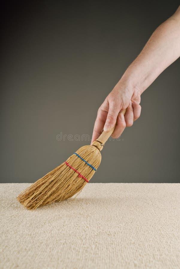 De vrouwelijke hand veegt tapijt met korte handlebroom stock fotografie
