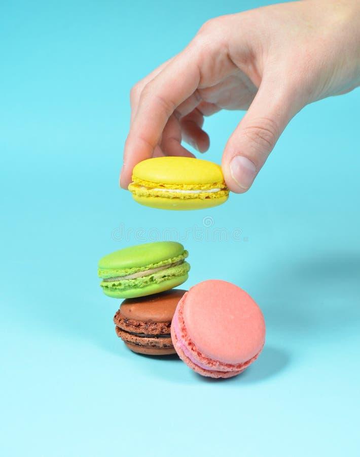 De vrouwelijke hand vermindert de gele makaronskoekjes Een stapel gekleurde makarons op een blauwe pastelkleurachtergrond minimal stock afbeeldingen