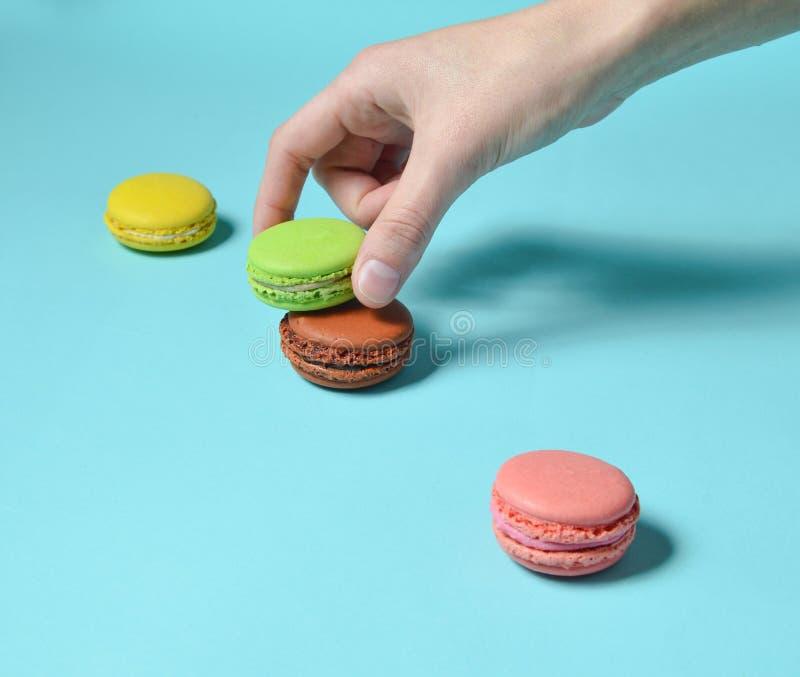De vrouwelijke hand vermindert de groene makaronskoekjes Een stapel gekleurde makarons op een blauwe pastelkleurachtergrond minim stock foto's