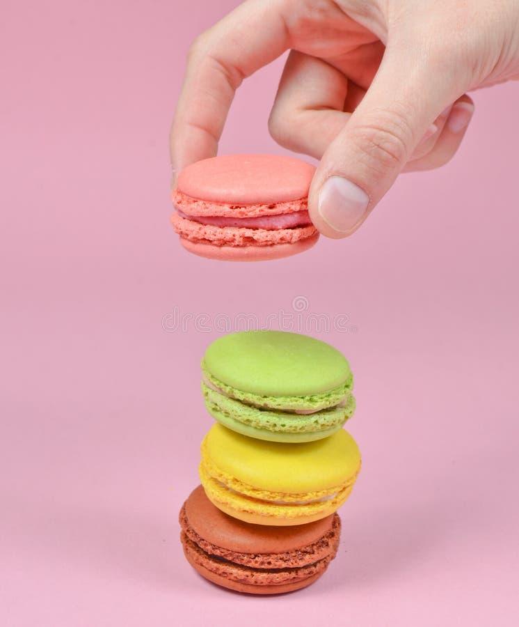 De vrouwelijke hand vermindert de roze makaronskoekjes Een stapel makarons op een roze pastelkleurachtergrond minimalism royalty-vrije stock foto's