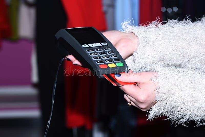 De vrouwelijke hand zet bankkaart in lezer defocused achtergrond stock foto