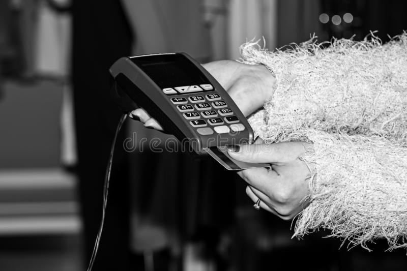 De vrouwelijke hand zet bankkaart in lezer defocused achtergrond stock afbeelding