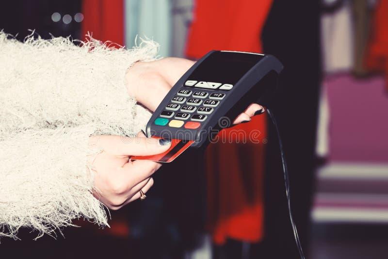 De vrouwelijke hand zet bankkaart in lezer defocused achtergrond stock foto's