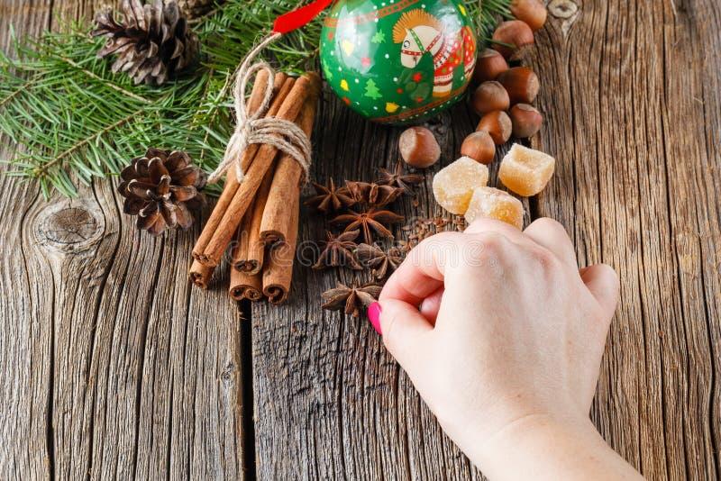 De vrouwelijke hand zet Kerstmiskruiden, kaneel, anijsplant stock afbeeldingen