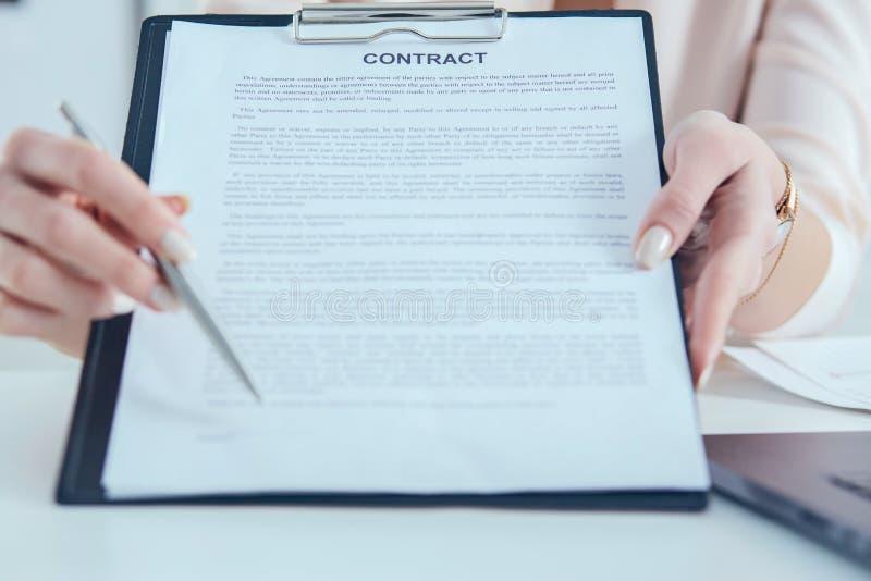 De vrouwelijke handen bieden contractvorm op klembordstootkussen en zilveren pen aan tekenclose-up aan royalty-vrije stock fotografie