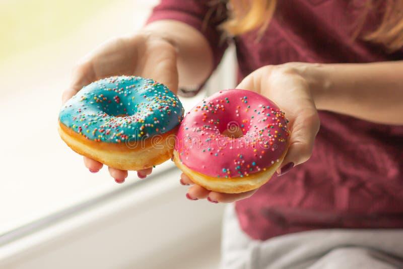 De vrouwelijke handen die zoete donuts houden met bestrooit stock fotografie