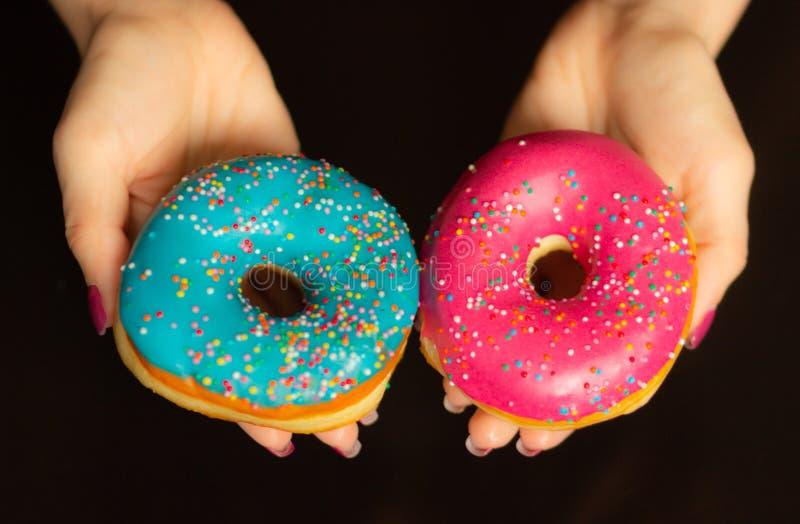 De vrouwelijke handen die zoete donuts houden met bestrooit op zwarte achtergrond, close-up royalty-vrije stock foto's