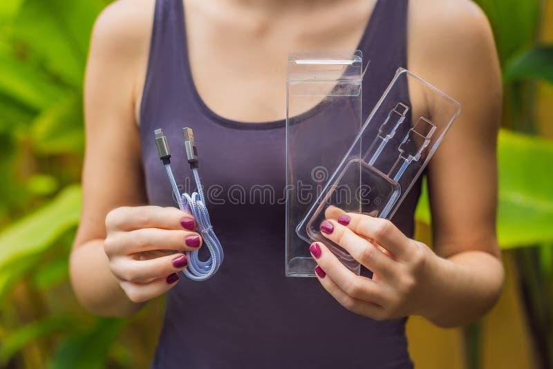 De vrouwelijke handen drukten een nieuwe draad om de telefoon te laden De draad werd ingepakt in een groot aantal van plastic ver royalty-vrije stock foto