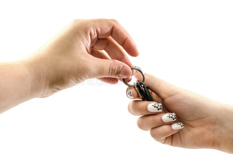 De vrouwelijke handen gaan de sleutels op een witte achtergrond over Close-up stock foto's