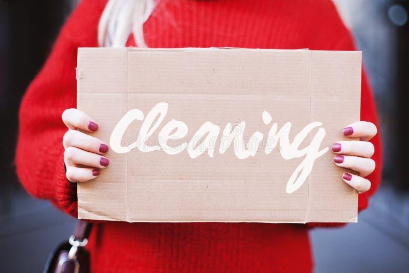 De vrouwelijke handen houden een kartontablet met het woord 'schoonmakend ', close-up stock afbeelding