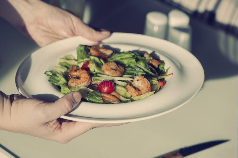 De vrouwelijke handen houden een plaat met garnalensalade Het concept het eten en gezonde levensstijlen royalty-vrije stock afbeelding