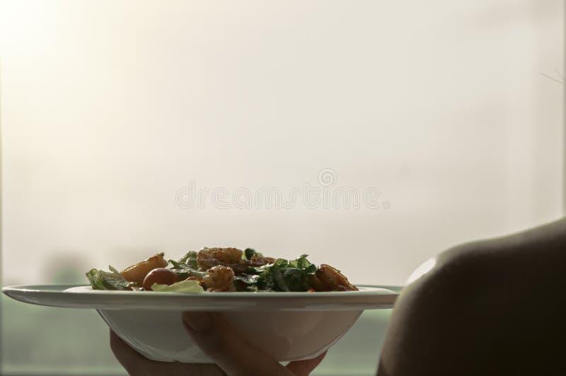 De vrouwelijke handen houden een plaat met garnalensalade Het concept het eten en gezonde levensstijlen stock foto's