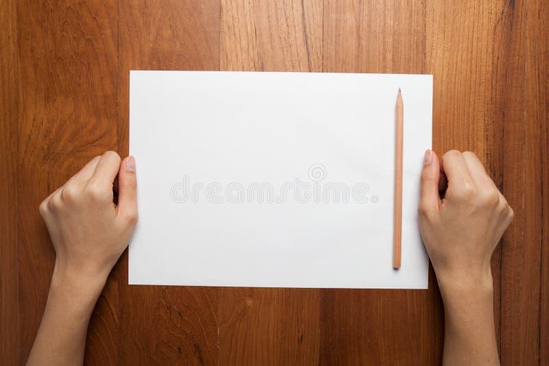 De vrouwelijke handen houden (greep) een uitstekende (oude) boek (nota, agenda) sprea stock fotografie
