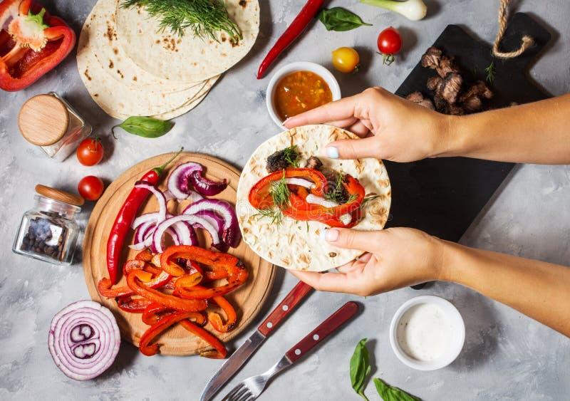 De vrouwelijke handen houden Mexicaanse taco's op concrete achtergrond cooking stock afbeelding