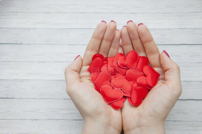 De vrouwelijke handen houden vele rode harten in de palm op een houten achtergrond, concept besparingsliefde stock afbeelding