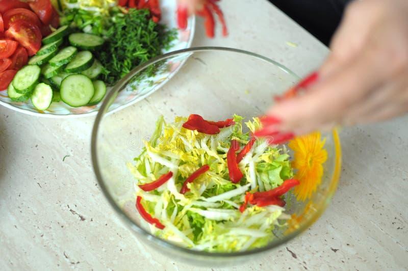 De vrouwelijke handen koken plantaardige salade bij de keuken stock afbeelding
