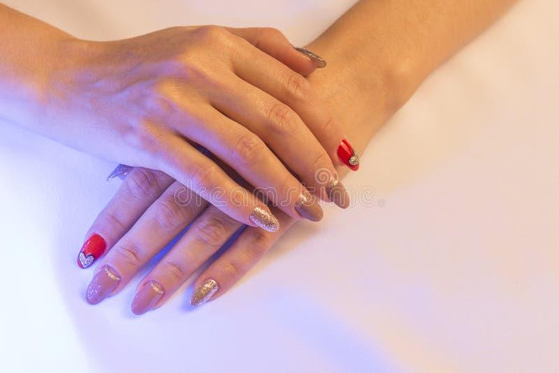 De vrouwelijke handen liggen bovenop elkaar, die een mooie met de hand gemaakte kunstmanicure op een lichte stoffenachtergrond to royalty-vrije stock afbeelding
