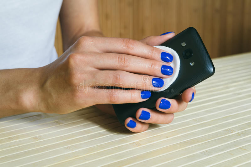 De vrouwelijke handen maken van stof en vuil een mobiele telefoon schoon royalty-vrije stock afbeelding