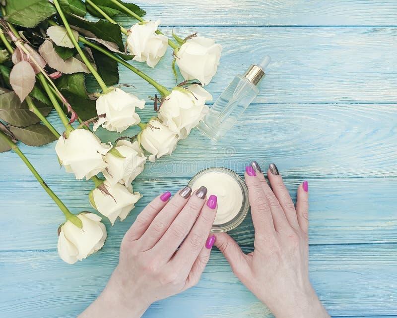 De vrouwelijke handen, manicure, kosmetische room, namen bloem op houten achtergrond toe stock foto's