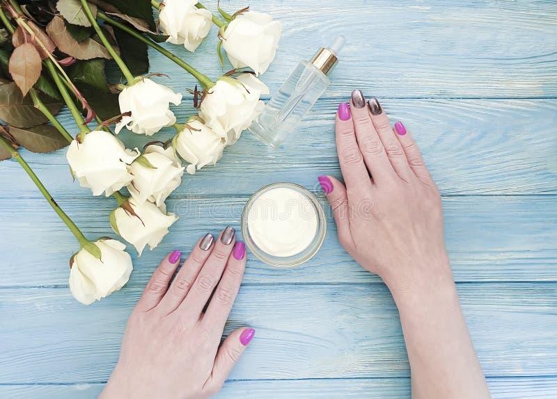 De vrouwelijke handen, manicureaard, gezondheids kosmetische room, namen bloem op houten achtergrond toe royalty-vrije stock afbeeldingen