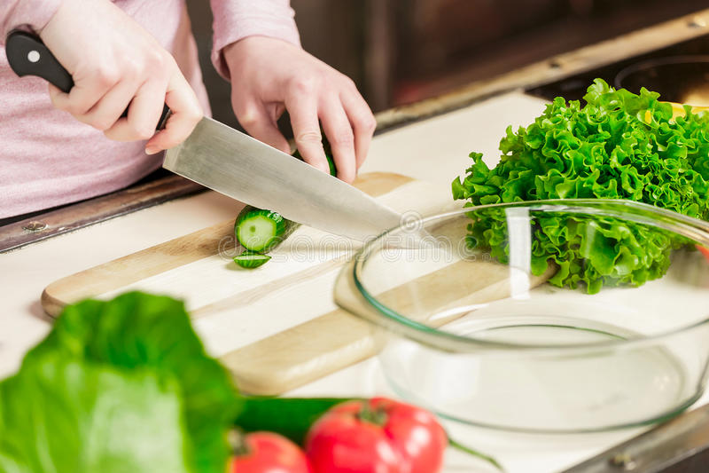 De vrouwelijke handen met een mes sneden verse komkommer op een houten raad Op de lijst in de keuken zijn groenten royalty-vrije stock afbeeldingen