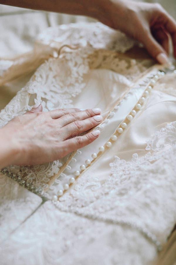 De vrouwelijke handen met mooie manicure raken witte huwelijkskleding met kant en knopenclose-up stock foto