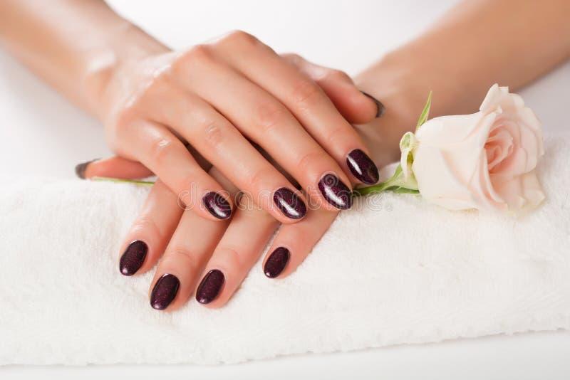 De vrouwelijke handen met purper spijkerspoetsmiddel met klatergoud op witte handdoek en roze namen op witte achtergrond toe stock foto's