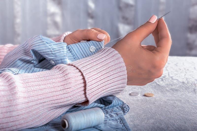 De vrouwelijke handen naaien een knoop stock fotografie