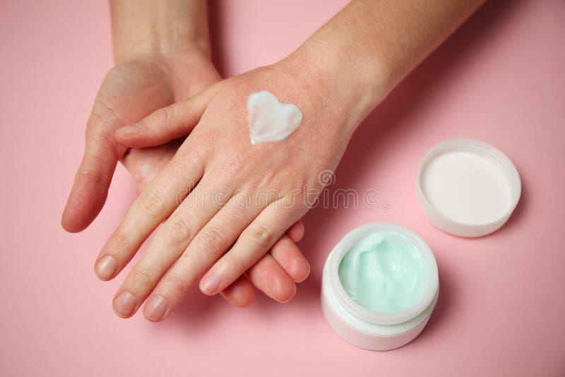 De vrouwelijke handen passen vochtinbrengende cr?me op de huid toe Irritatie en allergie?n, bevriezing royalty-vrije stock afbeeldingen
