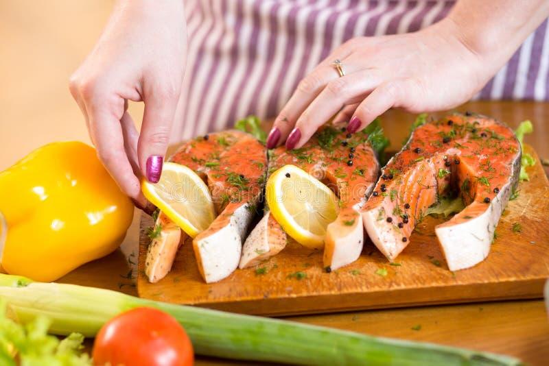 De vrouwelijke handen sluiten omhoog het koken vissen in binnenlands royalty-vrije stock afbeelding